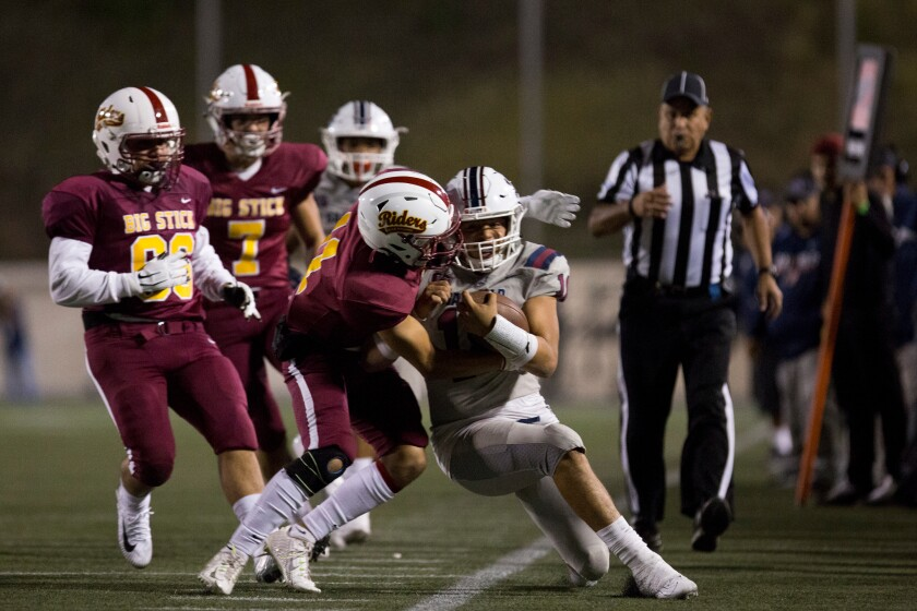 Garfield quarterback Jonathan Bautista is pushed out of bounds against Roosevelt in the East L.A. Classic on Friday night.