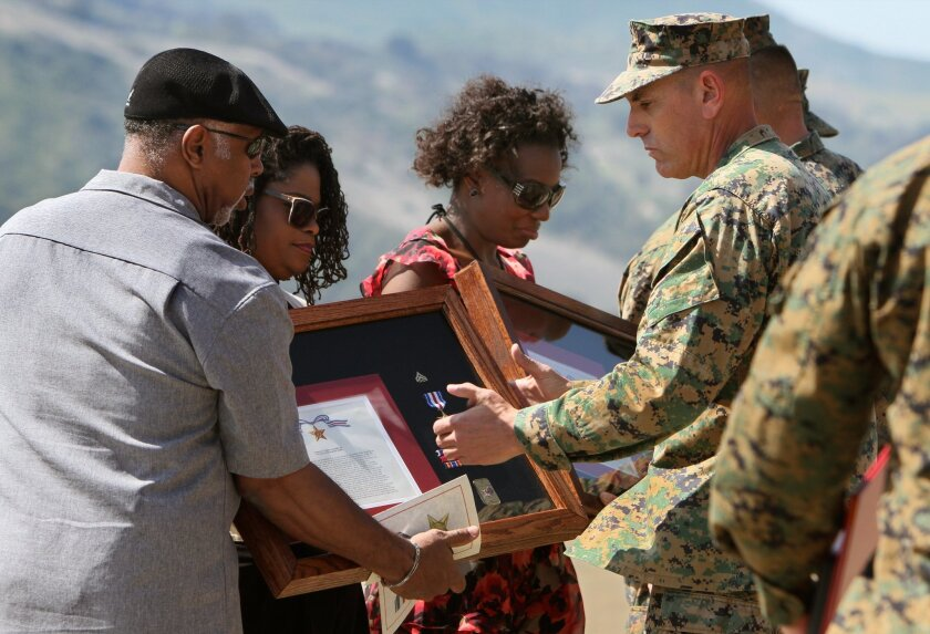 Marine Sgt. Major Scott Samuels presents a plaque to Lora and Bruce Merriweather, parents of Marine Cpl. Larris Harris, Jr., for the Silver Star Medal for heroism in Afganistan where Harris was killed in action. At right is Stacia Harris, wife of Larry Harris, Jr.