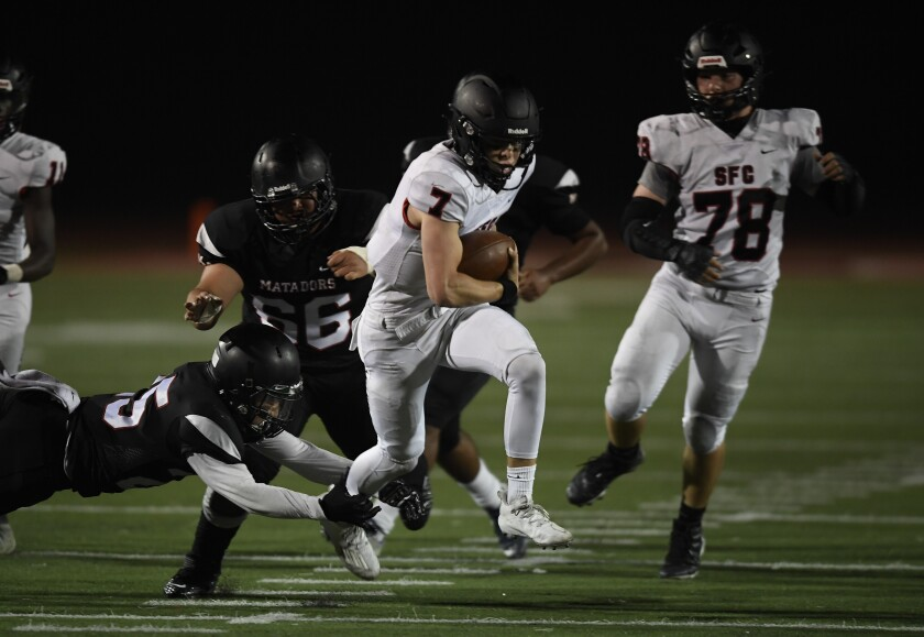 Santa Fe Christian quarterback Thomas Greupner tries to break away from Mt Miguel defenders.