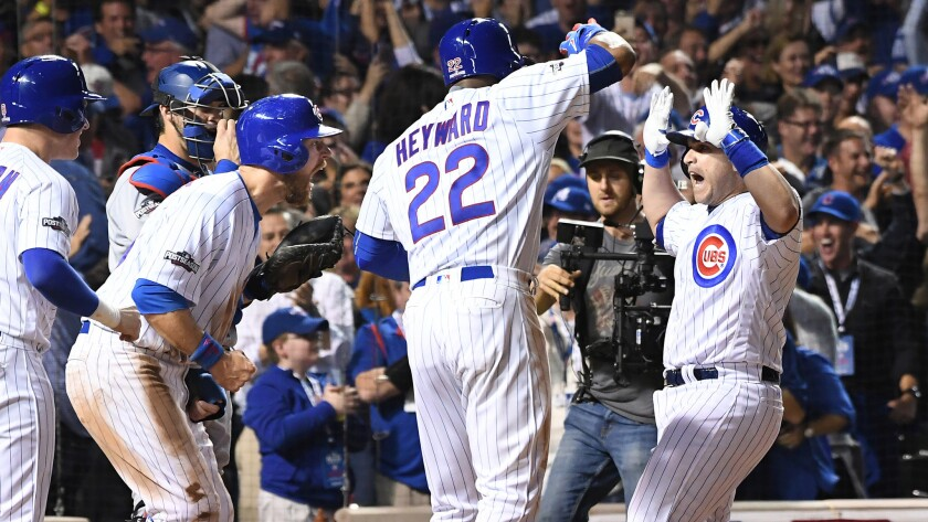 Cubs pinch-hitter Miguel Montero, right, is greeted by teammates after hitting a tiebreaking grand slam homer against the Dodgers in the eighth inning of Game 1.