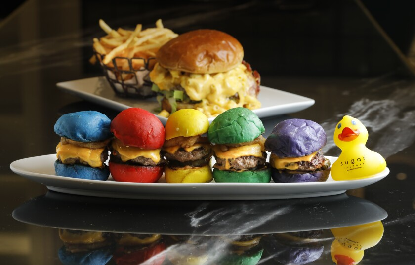 The Sugar Factory's multi-colored sliders aren't just a gimmick. In the background is a mac 'n cheese topped burger, The Big Cheesy.