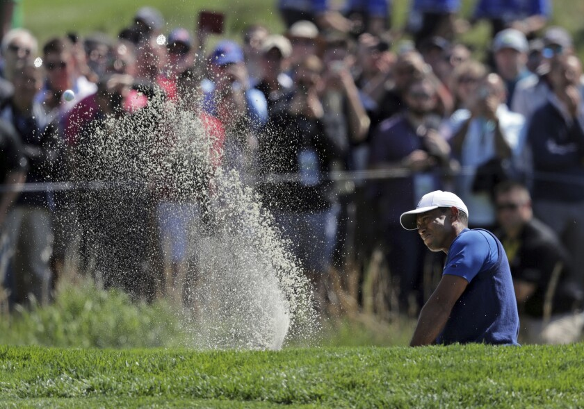 Tiger Woods hits out of a bunker on the 16th hole during the first round of the PGA Championship golf tournament, Thursday at Bethpage Black in Farmingdale, N.Y.