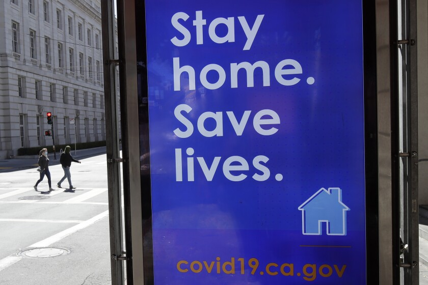 A sign advising people to stay home due to COVID-19 concerns is shown at a MUNI bus stop in San Francisco, Thursday, April 2, 2020.
