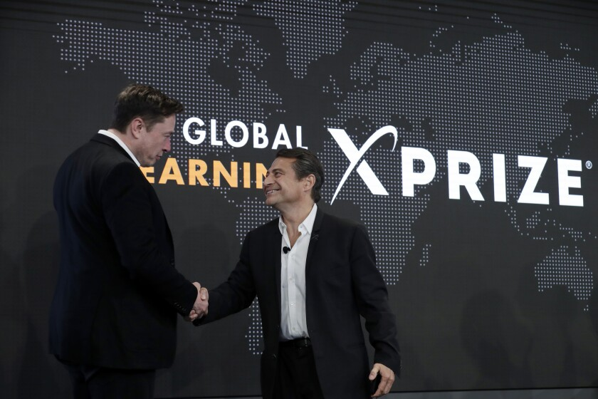 FILE - Tesla CEO Elon Musk, left, shakes hands with XPRIZE founder and Executive Chairman Peter Diamandis during the presentation of the XPRIZE for Children's Literacy in Los Angeles, in this Wednesday, May 15, 2019, file photo. Organizers of a $20 million contest to develop products from greenhouse gas that flows from power plants announced two winners Monday, April 19, 2021, ahead of launching a similar but much bigger competition backed by Elon Musk. Both winners made concrete that trapped carbon dioxide, keeping it out of the atmosphere, where it can contribute to climate change. Production of cement, concrete's key ingredient, accounts for 7% of global emissions of the greenhouse gas, said Marcius Extavour, XPRIZE vice president of climate and energy.(AP Photo/Marcio Jose Sanchez, File)