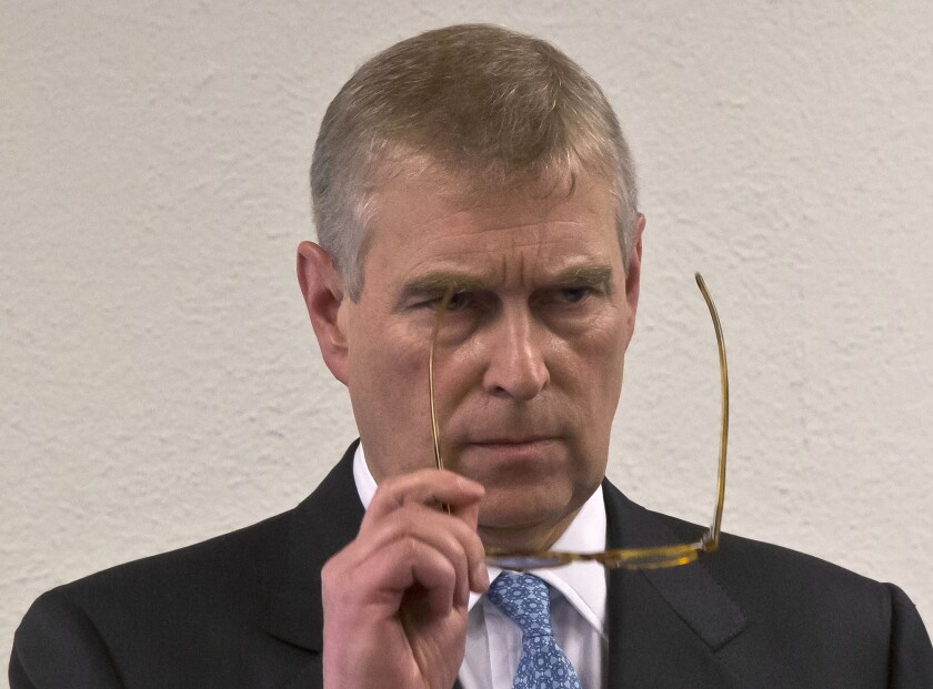 "FILE - In this file photo dated Thursday, Jan. 22, 2015, Britain's Prince Andrew, puts on his glasses prior to his speech to business leaders during a reception at the sideline of the World Economic Forum in Davos. Britain's Prince Andrew said Wednesday Nov. 20, 2019, that he is stepping back from public duties with the queen's permission, saying that recent disclosures regarding his association with the late convicted sex offender Jeffrey Epstein have become a ""major distraction"" to the royal family's work. (AP Photo/Michel Euler, FILE)"