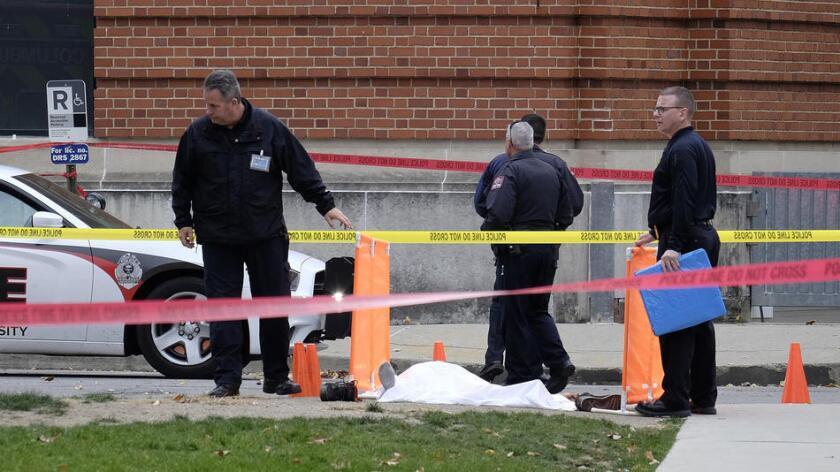 La policía cubre el cuerpo del sospechoso de haber atropellado, y herido a varias personas con un cuchillo, en la Universidad Estatal de Ohio. Foto: Adam Cairns / The Columbus Dispatch.