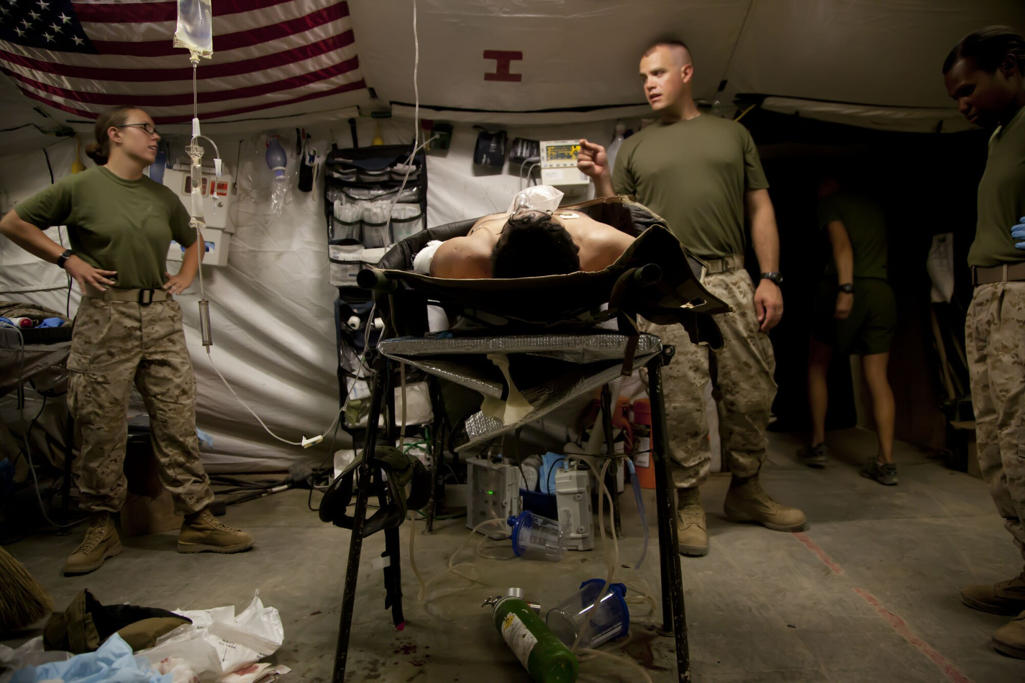 In June 2012, medical personnel at Forward Operating Base Edinburgh, in Helmand Province, discuss a patient's case.