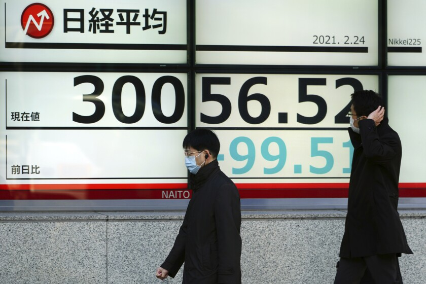 People wearing protective masks walk in front of an electronic stock board showing Japan's Nikkei 225 index at a securities firm Wednesday, Feb. 24, 2021, in Tokyo. Shares fell in Asia on Wednesday as investors weighed the possibility that inflation might prompt central banks to adjust their ultra-low interest rate policies. (AP Photo/Eugene Hoshiko)