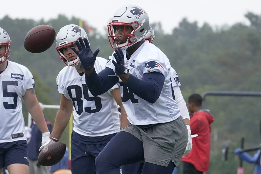 New England Patriots tight end Jonnu Smith, right, catches the ball while performing a field drill as tight end Hunter Henry (85) looks on during an NFL football practice, Wednesday, July 28, 2021, in Foxborough, Mass. (AP Photo/Steven Senne)