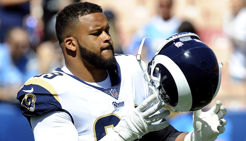 Los Angeles Rams defensive tackle Aaron Donald (99)gets ready to put on his helmet during warm-ups b