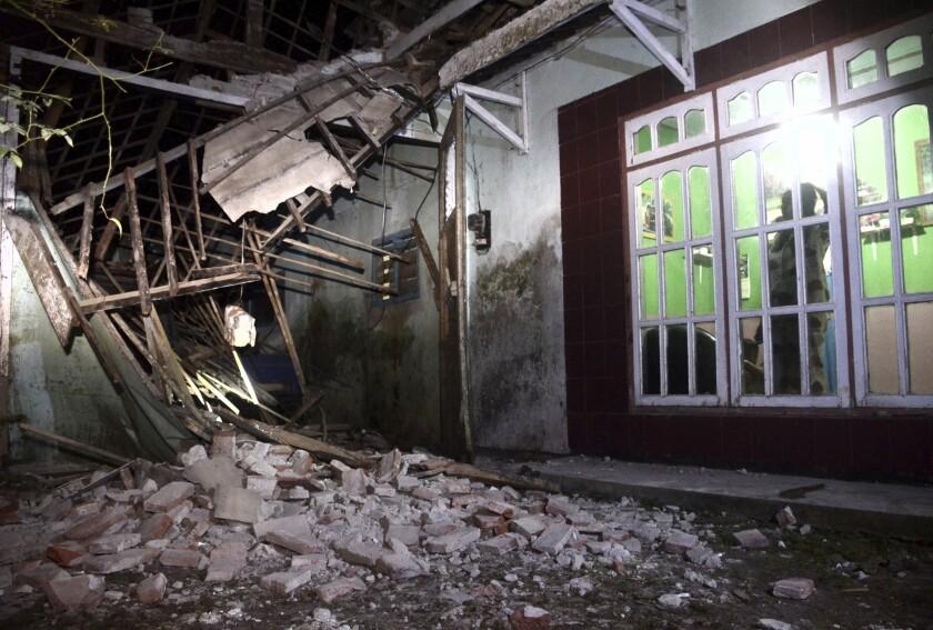 Una mujer inspecciona parte de su casa dañada por un sismo en Malan, en Java Orienal, Indonesia