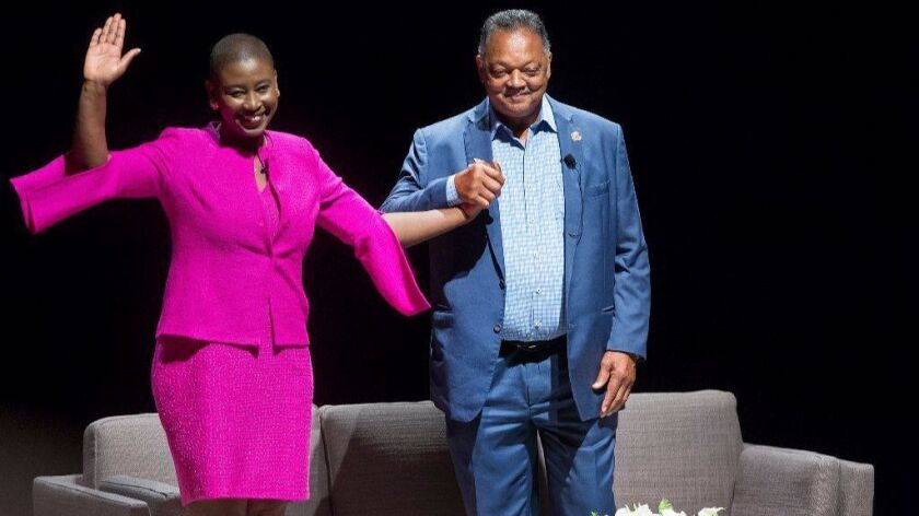 The Rev. Jesse Jackson greets the audience Friday with UC Irvine Professor Michele Goodwin during a