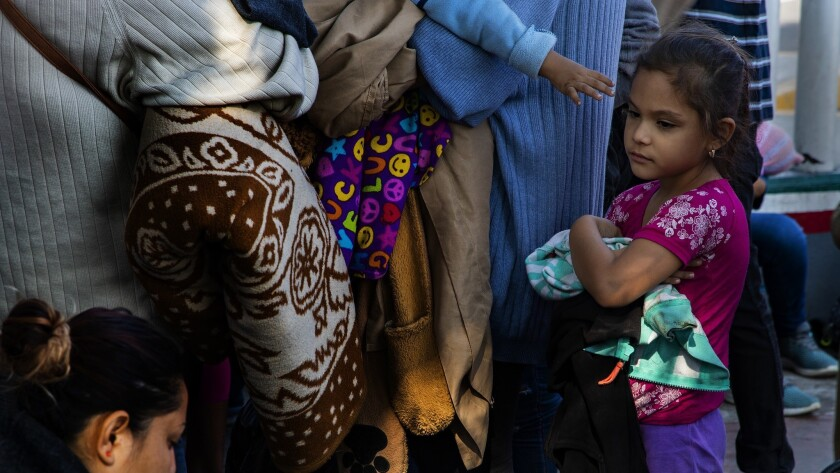 TIJUANA, MEXICO - JULY 3, 2018: A young boy reaches towards his sister as immigrant mothers with th