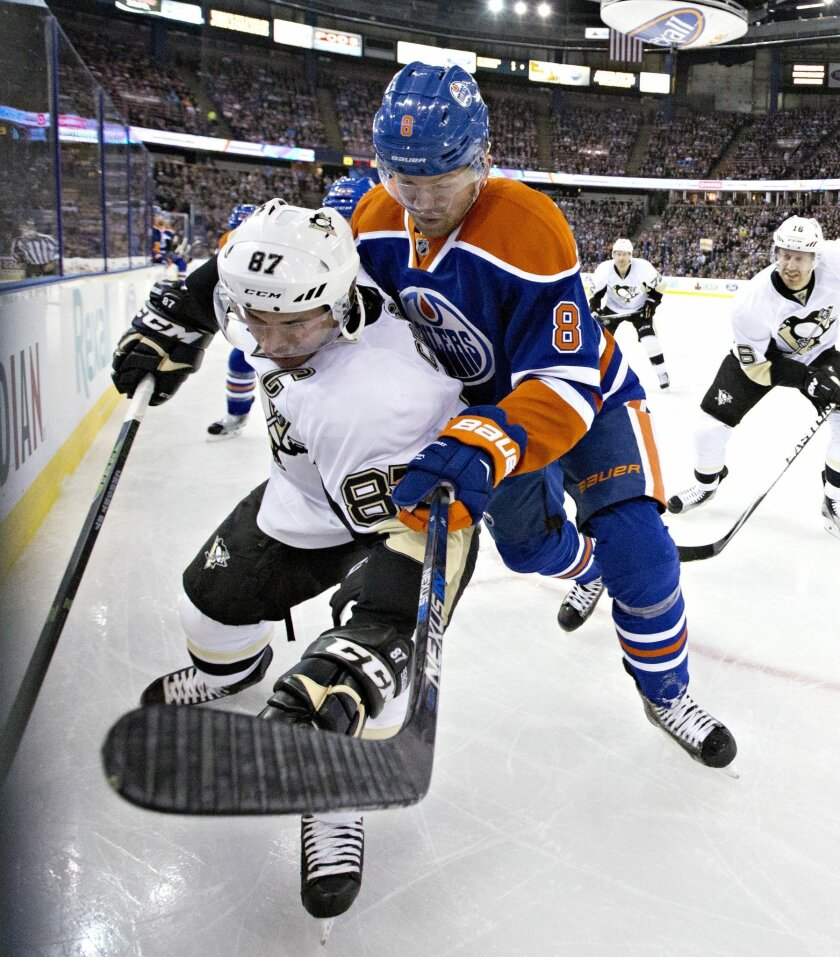 Pittsburgh Penguins' Sidney Crosby (87) battles with Edmonton Oilers' Griffin Reinhart (8) during the first period of an NHL hockey game Friday, Nov. 6, 2015, in Edmonton, Alberta. (Jason Franson/The Canadian Press via AP)