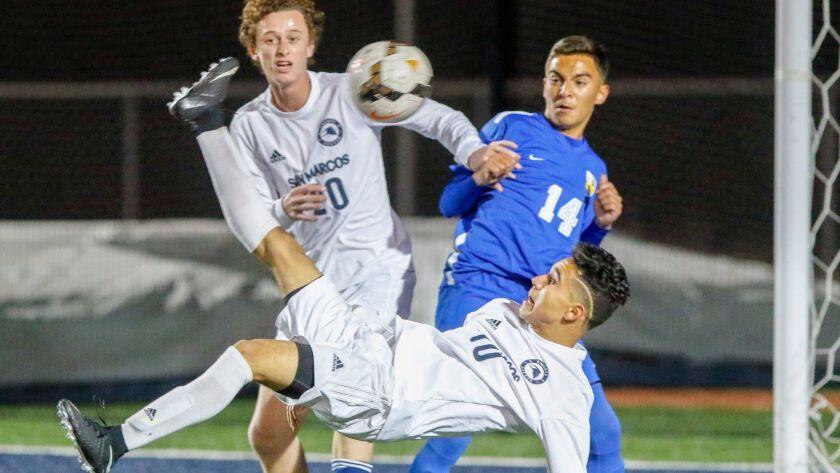 San Marcos' Ryan Anderson and San Pasqual's Cesar Caro look on as San Marcos' Pedro Mercado takes a