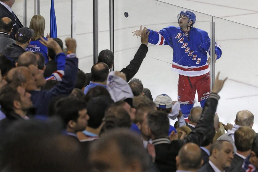 New York Rangers center Derick Brassard tosses the puck to fans after being named the game's most valuable player at the end of Game 1 in the first round of the NHL hockey Stanley Cup playoffs against against the Pittsburgh Penguins, Thursday, April 16, 2015, at Madison Square Garden in New York. T
