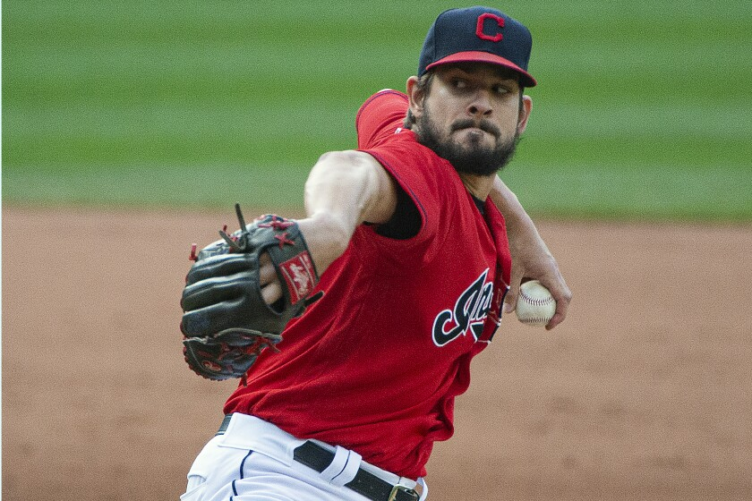 FILE - In this Sept. 27, 2020, file photo, Cleveland Indians relief pitcher Brad Hand delivers to Pittsburgh Pirates' Josh Bell during the ninth inning of a baseball game in Cleveland. The Cleveland Indians have declined contract options on Brad Hand and first baseman Carlos Santana for next season, decisions that will initially cut $27 million from the team's payroll. (AP Photo/Phil Long, File)