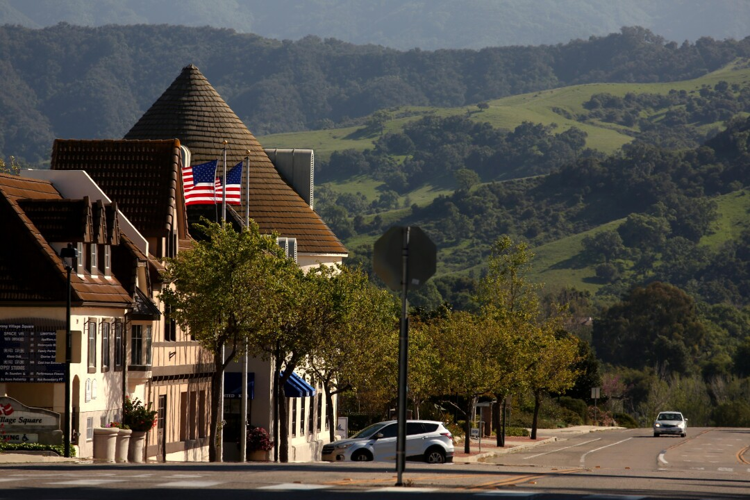 A lone car drives down a deserted Alisal Road in downtown Solvang.