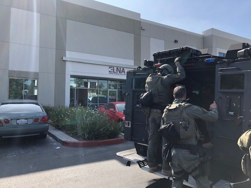 Chula Vista police arrive on an armored vehicle to shut down SB Discount Buds, a marijuana dispensary operated without a city business license in a Main Street warehouse.