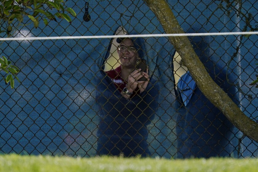 Fans look through holes in the fence along the 12th hole at the PGA Championship.