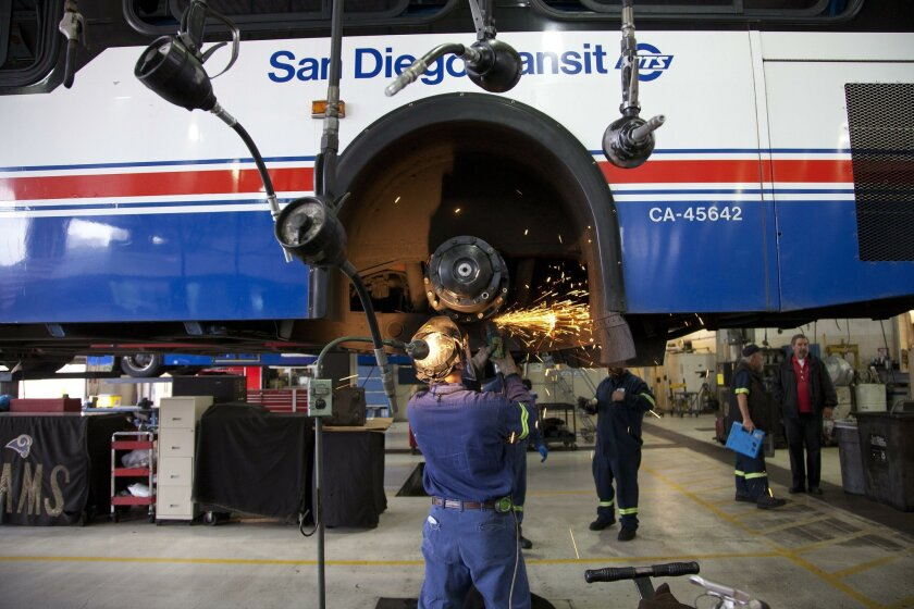 MTS mechanics work on buses in the maintenance bay in this 2013 photo. MTS allows for up to 20 percent of its fleet of buses to be down for scheduled or unscheduled maintenance work.