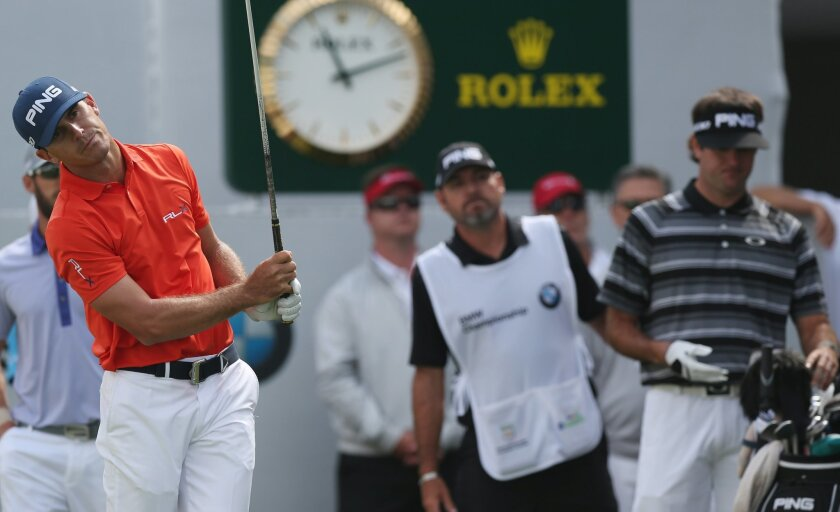 Billy Horschel, left, reacts to his tee shot on the first hole as Bubba Watson, right, pulls out a club in the third round of the BMW Championship golf tournament in Cherry Hills Village, Colo., Saturday, Sept. 6, 2014. (AP Photo/David Zalubowski)
