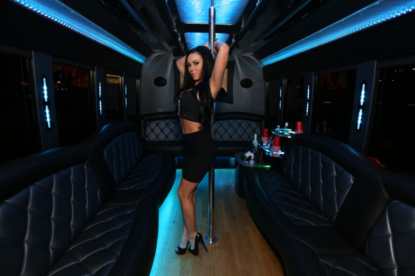 A model poses by the stripper pole aboard MaxVegas, the club-crawling coach now operating along Las Vegas Boulevard.