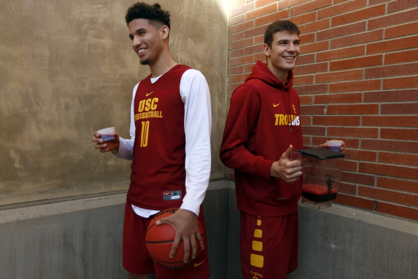 USC basketball players Bennie Boatwright, left, and Nikola Jovanovic, right, pose for a portrait holding beet juice, which they drink before every game.