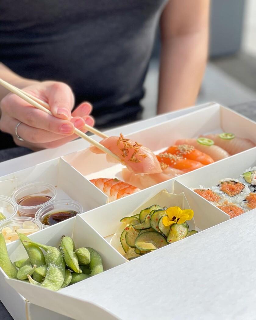 A Yakumi customized bento box of nigiri and sushi rolls.