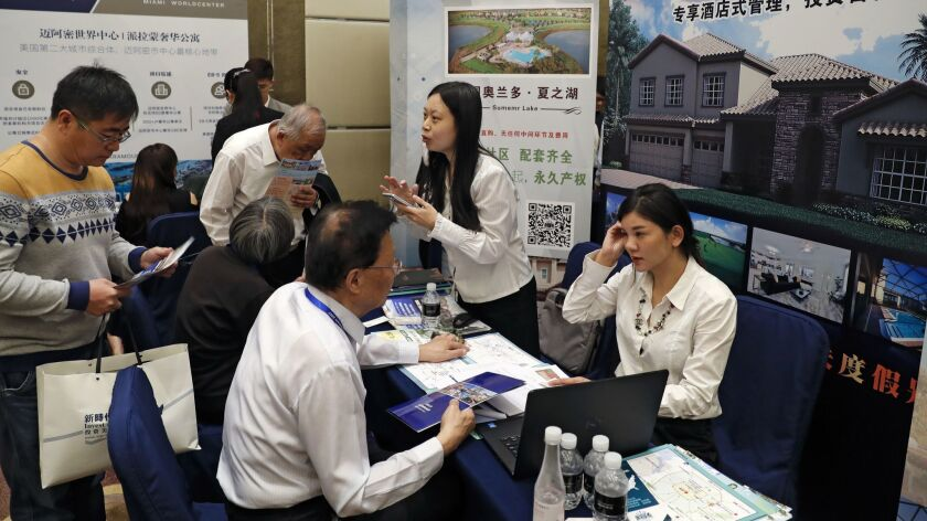 Chinese visitors seek information of the U.S. government's EB-5 visa program at the exhibitor booths