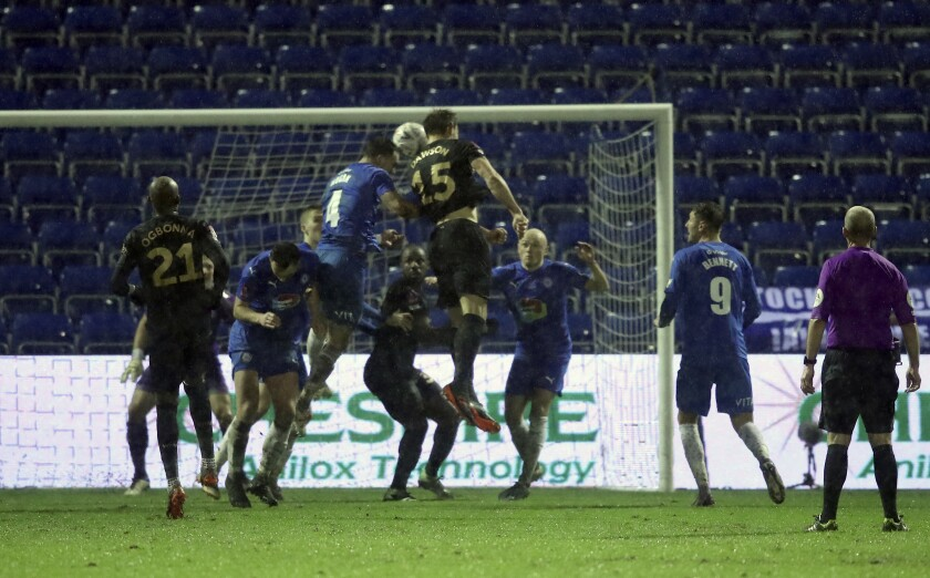 West Ham's Craig Dawson, centre, scores his side's opening goal during the English FA Cup third round soccer match between Stockport County and West Ham United at Edgeley Park in Stockport, England, Monday, Jan. 11, 2021. (Martin Rickett/Pool via AP)