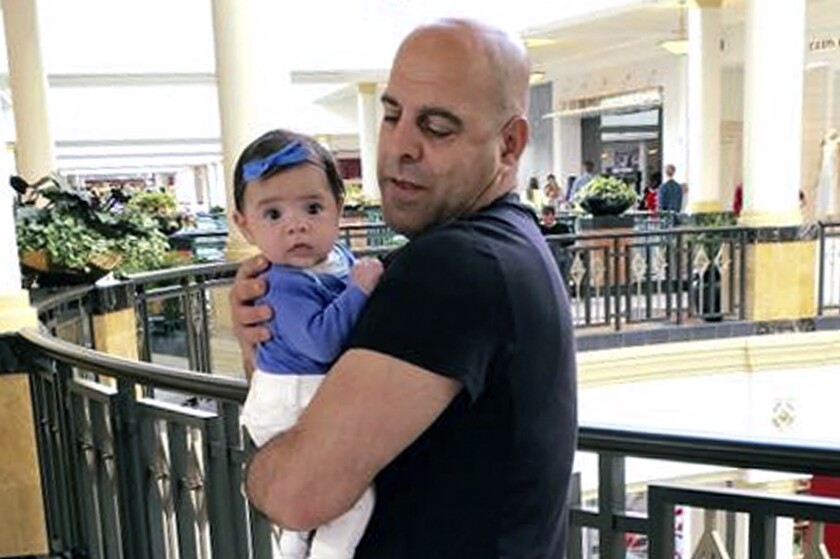 In this June 2016, photo provided by Guila Fakhoury, her father Amer Fakhoury holds his granddaughter, Kira, in King of Prussia, Penn. At a Senate Foreign Relations Committee hearing on Wednesday, Dec. 4, 2019, U.S. Sen. Jeanne Shaheen of New Hampshire said Fakhoury, an American citizen jailed in his native Lebanon since September 2019 on no charges is very ill and if he dies there, then Lebanon should be subject to sanctions. The 57-year-old restaurant owner was once part of the South Lebanon Army and worked at a former prison described by human rights groups as a center for torture. His family says he's innocent. (Guila Fakhoury via AP)