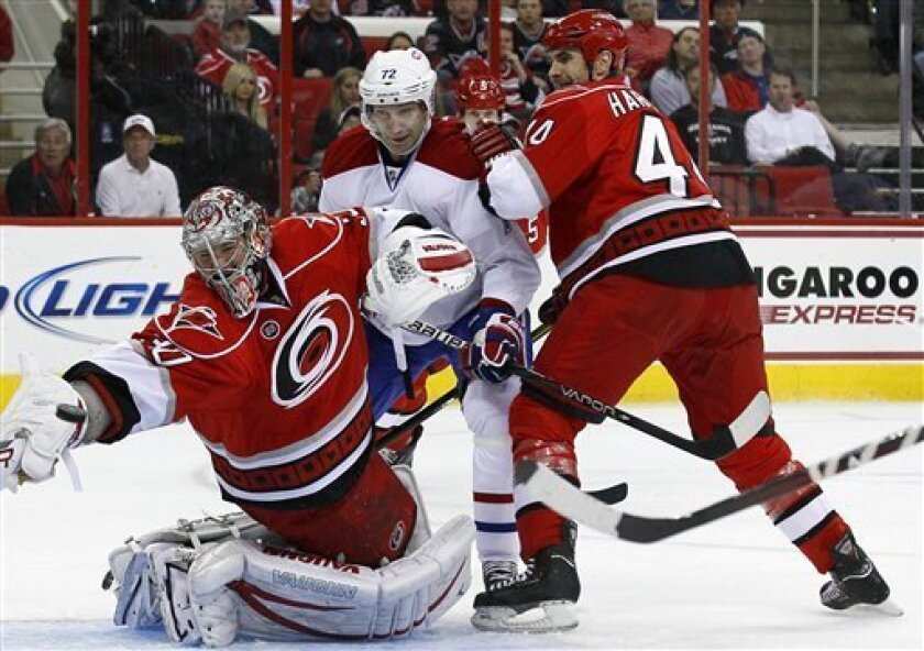 Carolina Hurricanes goalie Cam Ward deflects the puck as Jay Harrison (44) defends against Montreal Canadiens' Erik Cole (72) during the second period of an NHL hockey game in Raleigh, N.C., Thursday, April 5, 2012. (AP Photo/Gerry Broome)