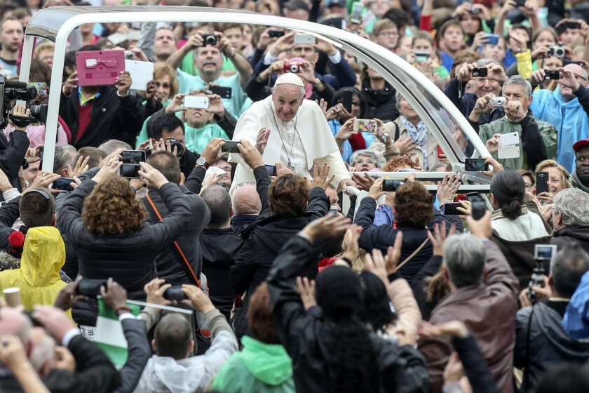"""Pope Francis greets visitors in St. Peter's Square at the Vatican. The pope has a new book deal with Random House. """"The Name of God Is Mercy: A Conversation with Andrea Tornielli"""" is to be released in January."""