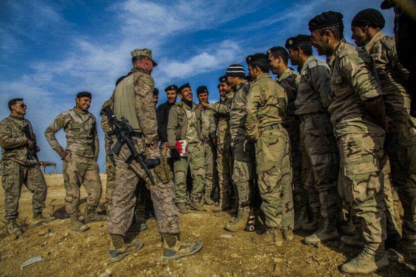 A U.S. Marine with Special Purpose Marine Air Ground Task Force-Crisis Response-Central Command, Task Force Al Asad, speaks with Iraqi soldiers during a break in training at Al Asad Air Base, Iraq, in support of an Operation Inherent Resolve Build Partner Capacity mission in January 2015. U.S. Marine Corps photo by Lance Cpl. Skyler E. Treverrow