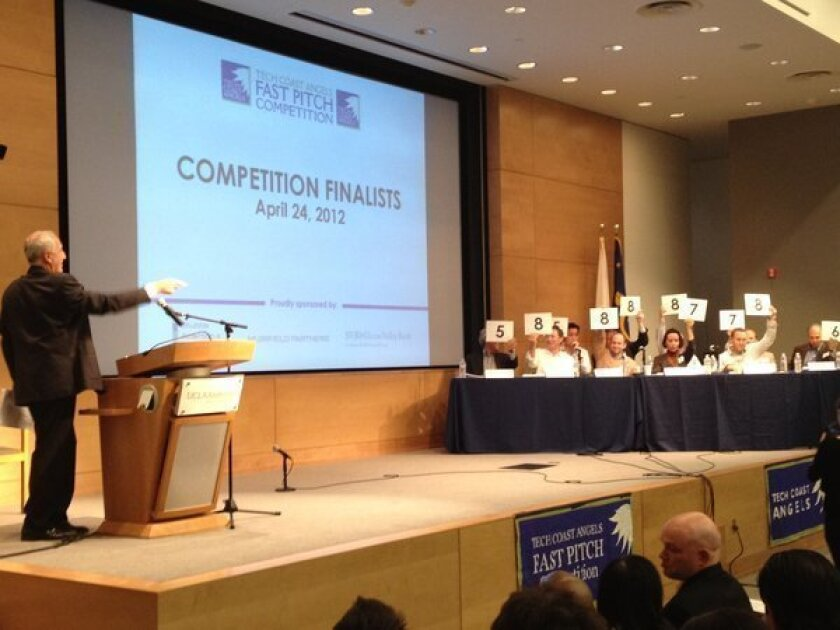 Judges hold up presentation scores for start-up Essio at Tech Coast Angels' Fast Pitch Competition at UCLA.