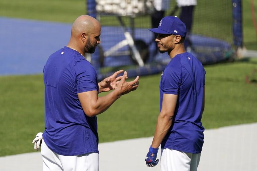 Dodgers first baseman Albert Pujols, left, speaks with right fielder Mookie Betts.