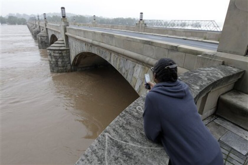 Lucy Mitchell looks at the high water level during flooding of the Susquehanna River caused by rainfall from the remnants of Tropical Storm Lee, as the water flows under the closed Market Street Bridge, Friday, Sept. 9, 2011, in Harrisburg, Pa. (AP Photo/Alex Brandon)