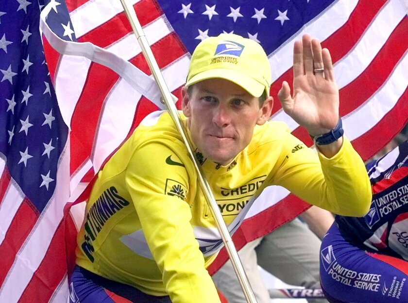 Lance Armstrong riding down the Champs Elysees with an American flag after the 21st and final stage of the Tour De France in 2000.