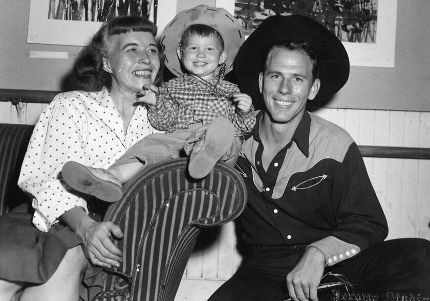 Une photo en noir et blanc d'un enfant en bas âge entre une femme, à gauche, et un homme