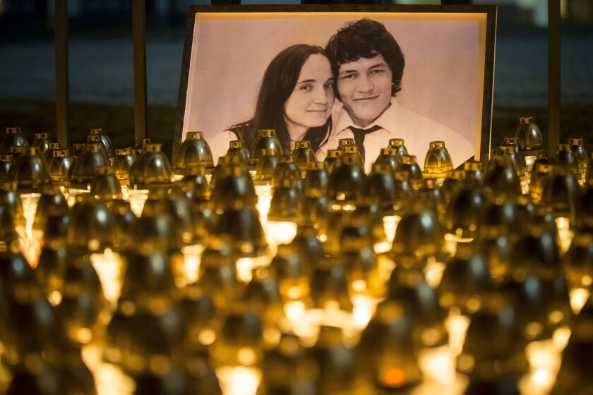 FILE - In this Wednesday, Feb. 28, 2018 file photo, light tributes are seen during a silent protest in memory of murdered journalist Jan Kuciak and his girlfriend Martina Kusnirova, seen in photo, in Bratislava, Slovakia. A court in Slovakia is expected to issue a verdict on Thursday Sept. 3, 2020, in the slayings of an investigative journalist and his fiancee, a crime that shocked the country and led a government to fall. (AP Photo/Bundas Engler, file)