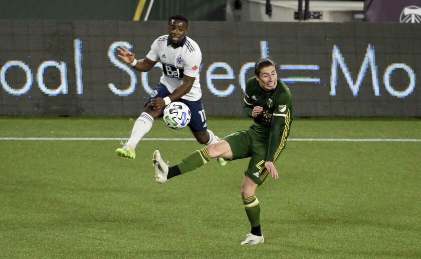 Vancouver Whitecaps forward Cristian Dajome, left, puts a shot on goal as Portland Timbers defender Jorge Villafana defends during the first half of an MLS soccer match in Portland, Ore., Sunday, Nov. 1, 2020. (AP Photo/Steve Dykes)