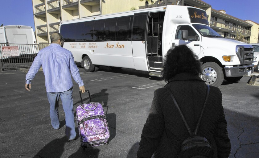 Passengers board a New Sun International Travel bus to Las Vegas from a hotel parking lot in Rosemead.