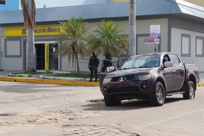 Police stand guard outside a bank in Milagres, Brazil, on Friday, Dec. 7. EFE-EPA/Normando Soracles
