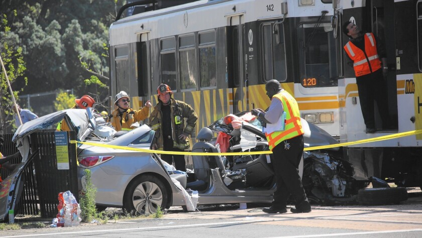 Emergency crews work to clear the site of a crash between a car and a Metro Expo Line train on Exposition Boulevard near USC.