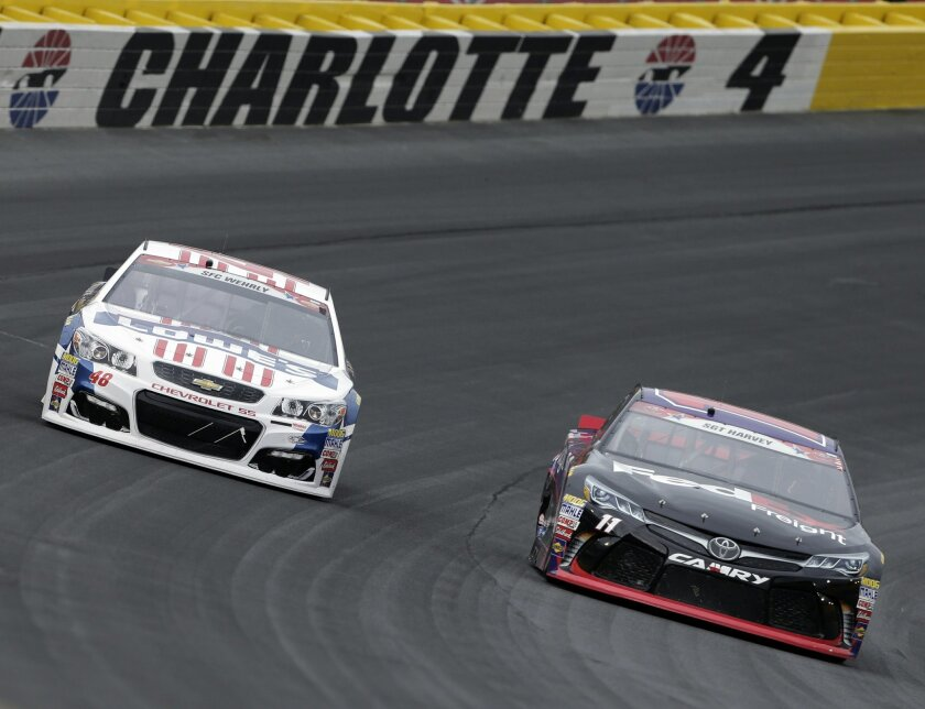 Denny Hamlin, right, races Jimmie Johnson, left, out of Turn 4 during the NASCAR Sprint Cup series auto race at Charlotte Motor Speedway in Concord, N.C., Sunday, May 29, 2016. (AP Photo/Chuck Burton)