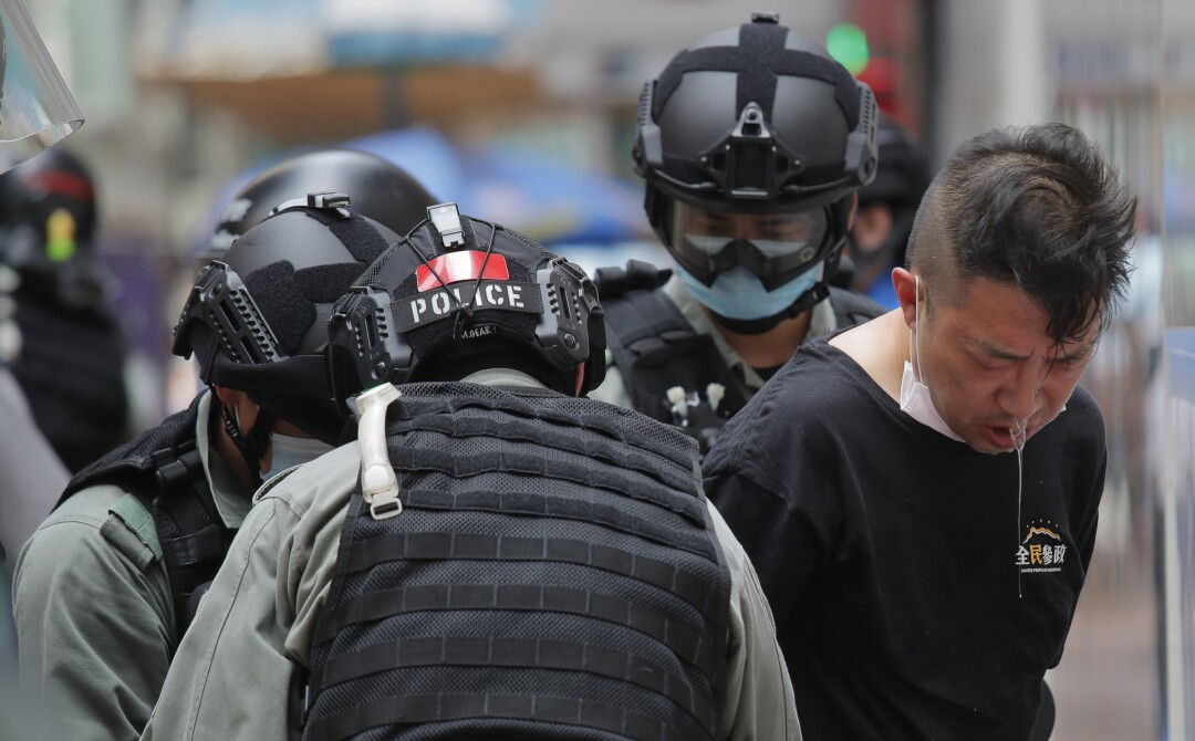 A protester who had been pepper sprayed is detained by Hong Kong police during Wednesday's protest.