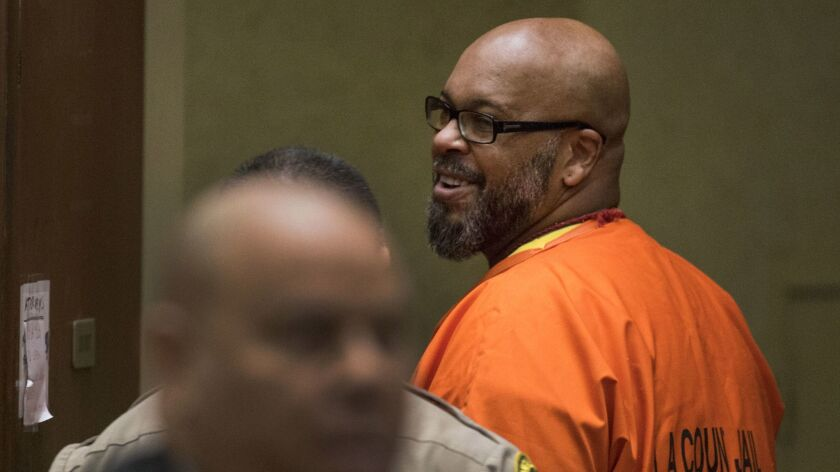 Suge Knight smiles at friends and family members in the courtroom.