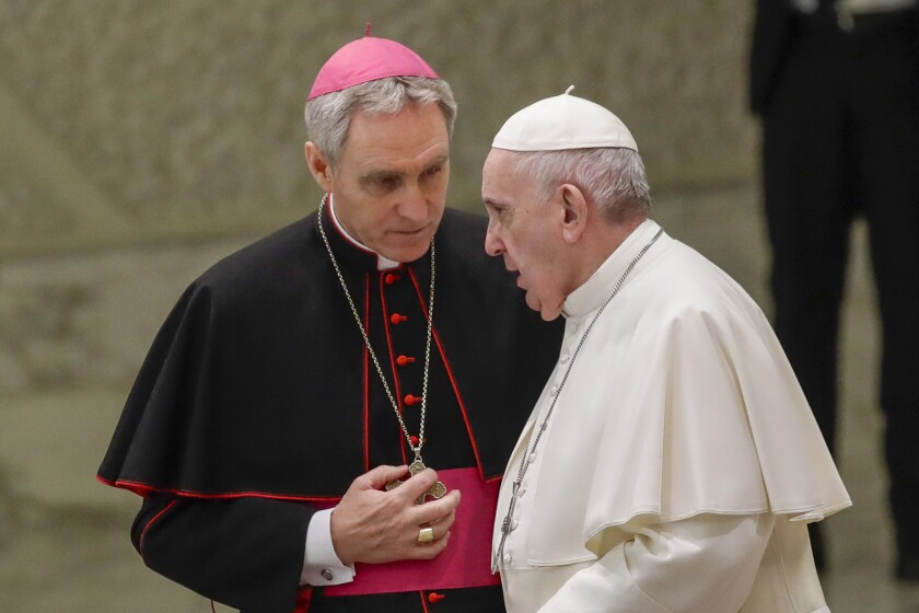 Pope Francis talks with Papal Household Archbishop Georg Gaenswein during his weekly general audience, in Paul VI Hall at the Vatican, Wednesday, Jan. 15, 2020. (AP Photo/Alessandra Tarantino)