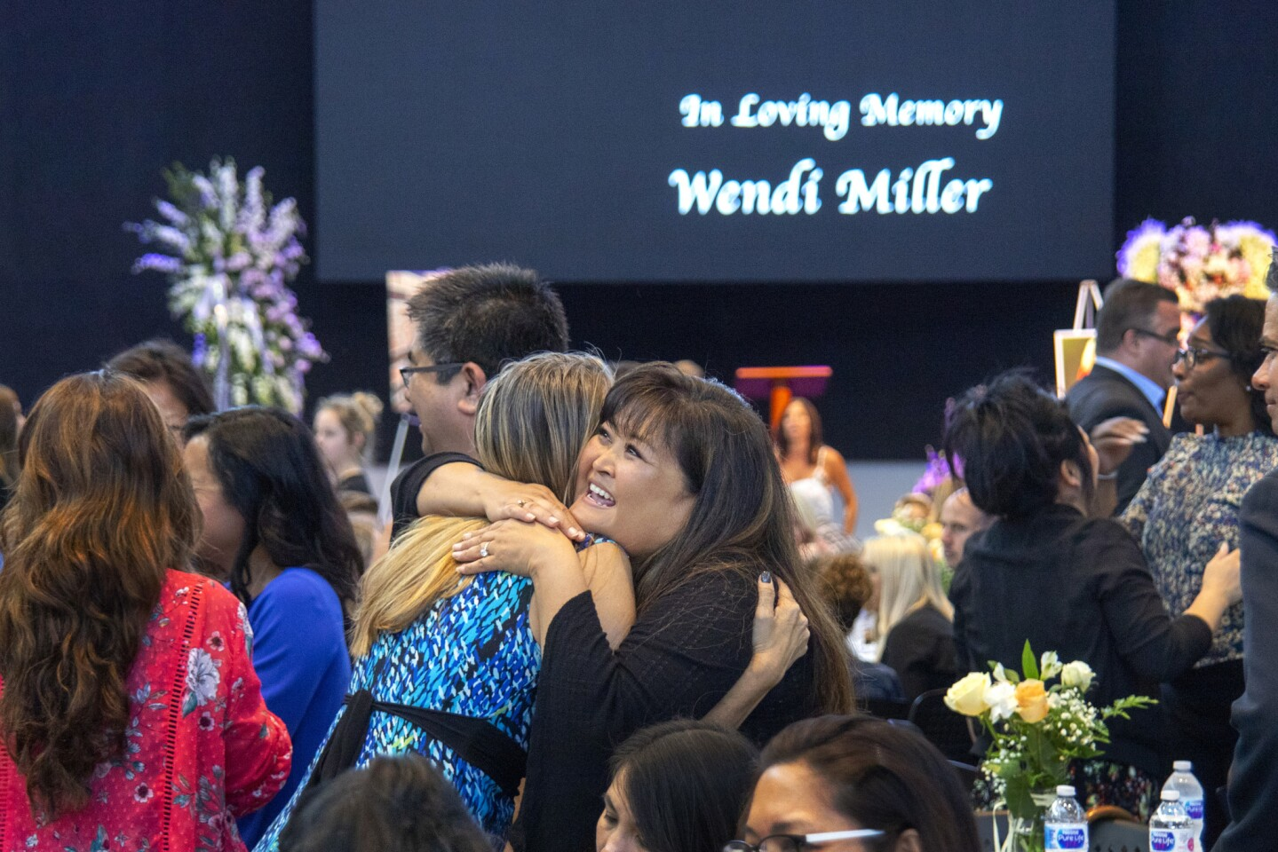 "With ""In Loving Memory Wendi Miller"" in the background, guests Brooke Castro and Wendy Morinish share an emotional hug at a service Friday at Mariners Church in Irvine."